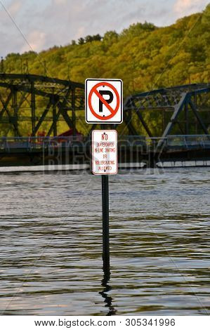 A Sign Partially Submerged In A Swollen River Does Not Allow Parking , Rollerskating, Or Skateboards