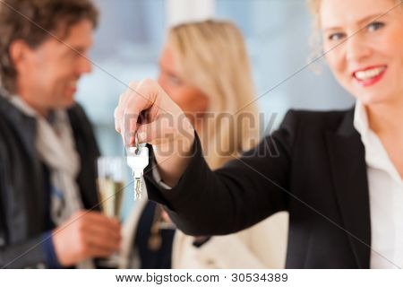 Real estate market - young couple looking for real estate to rent or buy; they celebrate with champagne and get the keys