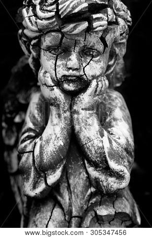 Old and cracked statue of Cherub little child