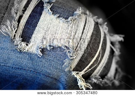 Frayed blue jeans with worn holes denim pants