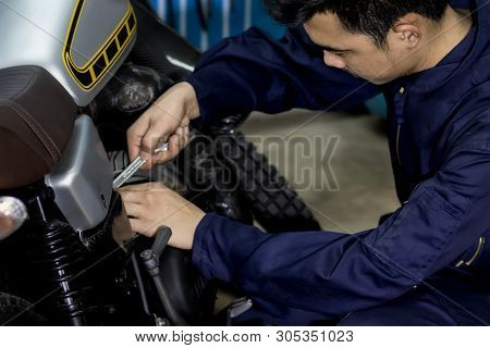 People Use Hand Are Repairing A Motorcycle Use A Wrench To Work. Use The Wrench To Tighten The Cylin