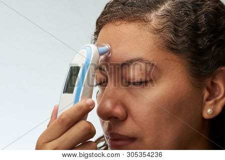 Checking Body Temperature Theme. Young Woman With Digital Thermometer Next To Forehead