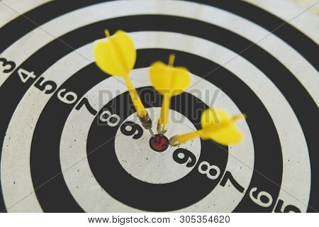 Three Yellow Dart On Board Right Direction Hit Target Goal. Competition Game To Win Focus On Achieve
