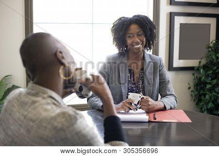 Black African American Female Businesswomen Talking In An Office.  The Two Women Looks Like A Start