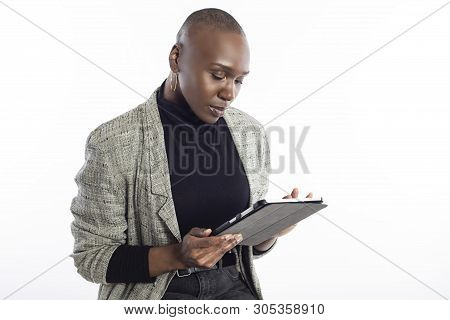 Black African American Female Teacher Preparing Her Course Or Lessons Online With A Tablet Computer.
