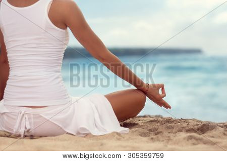 body of a beautiful girl in a meditation on the beach