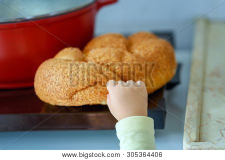 The Hand Of A Hungry Child Hold And Break A Piece Of Bread. A Kids Hand Tearing A Piece Of Challah.
