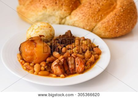 Close Up Challah Shabbat Bread And Hamin Or Cholent In Hebrew - Sabbath Traditional Food On White Ta
