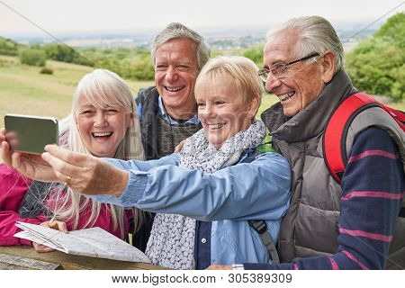Group Of Senior Friends Hiking In Countryside Standing By Gate  And Taking Selfie On Mobile Phone