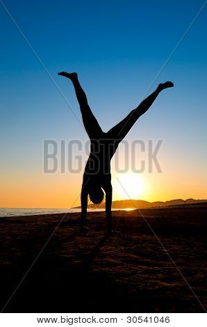 Woman Turning Cartwheel On Beach