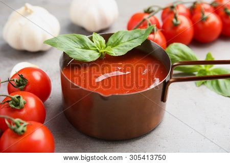Pan Of Tasty Tomato Sauce With Basil Served On Grey Table