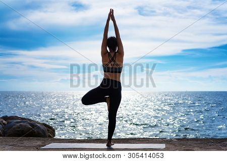 Portrait of young woman practicing yoga at the sea.Relax at the sea.Meditation