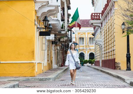 Beautiful woman on white dress walking alone at the streets of the colonial walled city of Cartagena de Indias poster