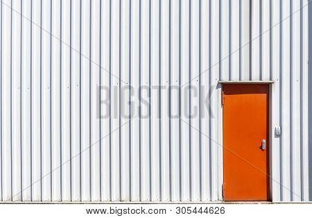 Industrial Building Facade With A Metal Orange Door And A White Aluminum Sheet Wall. White Warehouse