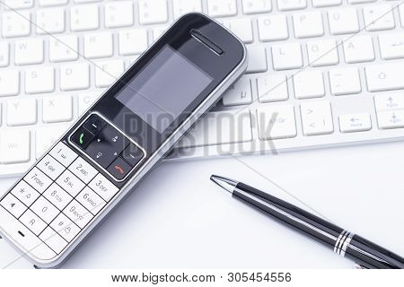 Image Shows A Phone On A Keyboard With A Pen Isolated On White