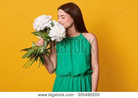Portrait Of Tender Adorable Woman Holding White Flowers In One Hand, Feeling Their Smell, Putting Th