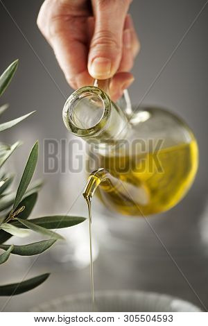 Preparing Healthy Meal With Olive Oil. Bottle Of Extra Virgin Oil Pouring In To Bowl. Healthy Food C