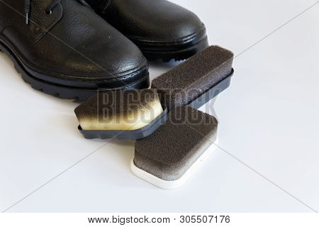 poster of Black shoes and Shoe sponge on white background. Shoe care with a Shoe sponge. Shoe sponge. No people
