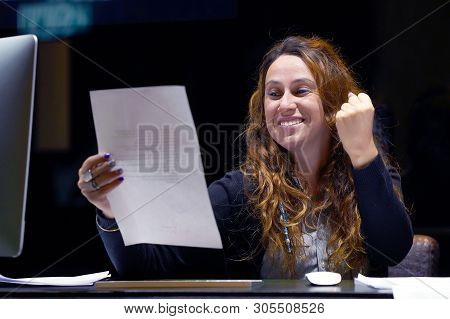 Close-up of an office worker. Happy lady, enjoying the good news in writing. An euphoric girl is happy after reading good news in a written letter, approving a loan, raising her job. poster