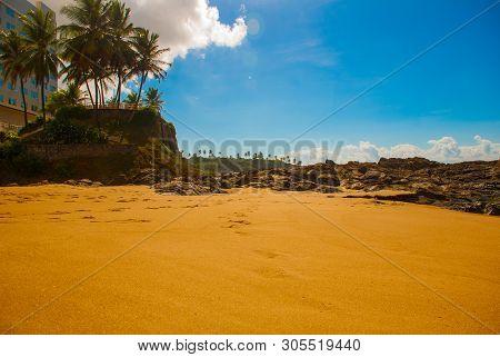 Salvador, Bahia, Brazil: Brazilian Beach With Yellow Sand And Blue Sea In Sunny Weather.