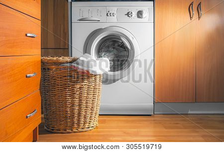 Large Wicker Laundry Basket, Lid Opened, Near The Front Load Washing Machine With Laundry. House Int