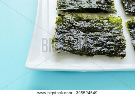 Dry Korean Organic Seaweed Isolated On Blue Background.crispy Seaweed.healthy Food Concept.top View,