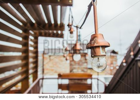 a garland of white light bulbs hangs on the ennobled roof of the house. wooden gazebo on the housetop overlooking the neighboring and sky. penthouse. poster