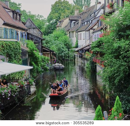 Colmar, France - Aug 2015: Pretty Canal Scene In Medieval Town With Old Half-timbered Homes, Flowers