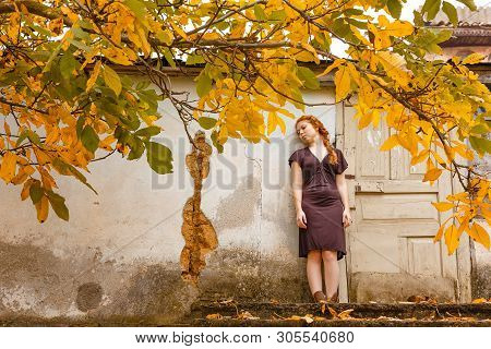 Sad Red-haired Girl Standing Near A Broken Window, The Concept Of Poverty And Misery.