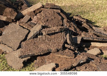A Close Uo View Of Old Tar Pieces Of A Driveway That Is Being Re-tarred.