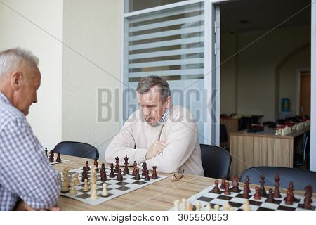Two Aged Experienced Grandmasters Practicing Chess Skills By Playing Together At Chess Club