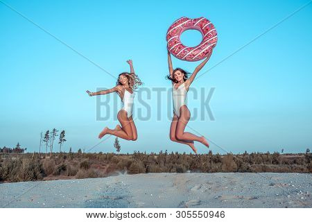 Two Girls Girlfriends Jumping Having Fun Playing With Inflatable Circle, White Sand, Sea Quarry, Lak