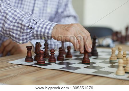 Tanned Wrinkled Hand Of Old Professional Grandmaster Making Decisive Chess Move During Intense Game