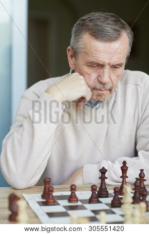 Puzzled Old Experienced Grandmaster With Wrinkled Forehead And Grey Beard Carefully Thinking About N
