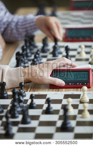 Wrinkled Hand Of Aged Experienced Grandmaster In Beige Sweater Gently Pressing Chess Clock