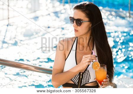 Pretty Young Slim Stylish Woman With Long Dark Hair By The Swimming Pool With A Cocktail Wearing Whi