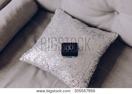 Two Engagement Rings Lie On A Stylish Pillow With Silver Sparkles. Selective Focus, Blurred Backgrou