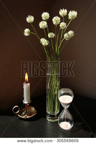 Still Life With Vintage Sandglass, White Or Dutch Clover Flowers In The Glass Vase And Burning Candl