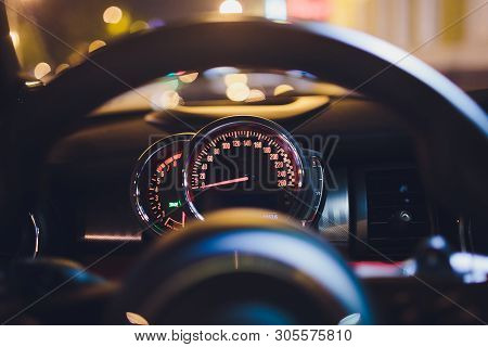 Speedometer Scoring High Speed In A Fast Motion. Sporty Car Dashboard Instruments Illuminated At Nig
