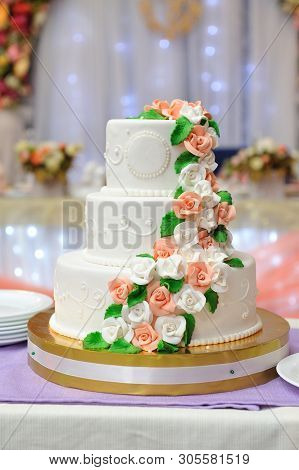 A Beautiful Three-tiered Wedding Cake Decorated With Mastic And Roses Molded From Flowers. Close-up