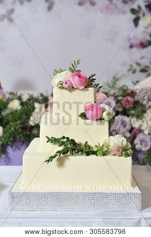 Beautiful three-tiered square-shaped wedding cake, decorated with beige cream, pistachio sprigs and peony flowers. Close-up poster