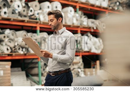 Manager Doing An Inventory Check On A Warehouse Floor