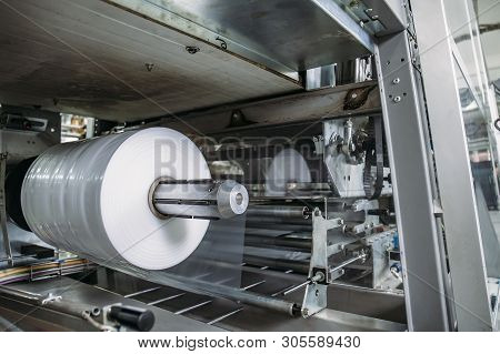 Plastic Roll In Industrial Food Packaging Machine Equipment Tool At Factory Workshop, Close Up