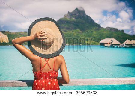 Beach vacation travel getaway summer holiday woman looking at view of Mt Otemanu on Bora Bora luxury hotel on romantic honeymoon. Tourist holding hat from behind enjoying Tahiti, French Polynesia.