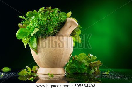 Herbs. Bunch of Fresh green organic aromatic herb leaves in wooden mortar with pestle over green background. Mint, Peppermint, Rosemary, Thyme, Sage in bowl. Green leaf of fragrant Mediterranean Herb