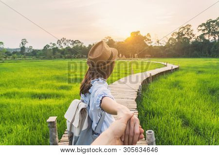 Young Woman Traveler Holding Man's Hand And Leading Him On Green Paddy Field, Couple Vacation Travel