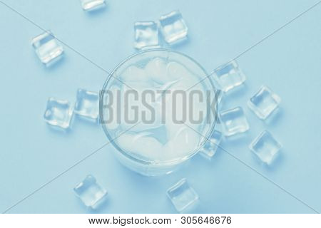 Glass of refreshing cold water with ice and ice cubes on a blue background. Concept of thirst, heat, refreshment in the summer. Flat lay, top view poster
