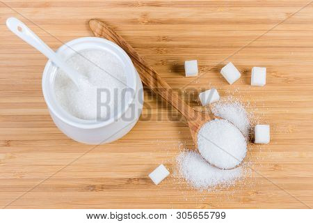 White Refined Table Sugar In Sugar-bowl, In Wooden Spoon And Scattered Beside To Her And Cubes Of Wh