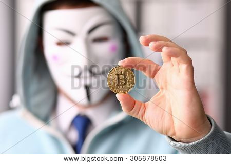 Minsk, Belarus, June, 2019: Hacker Wear Anonymus Mask Hold Bitcoin In Hand Illustrative Editorial