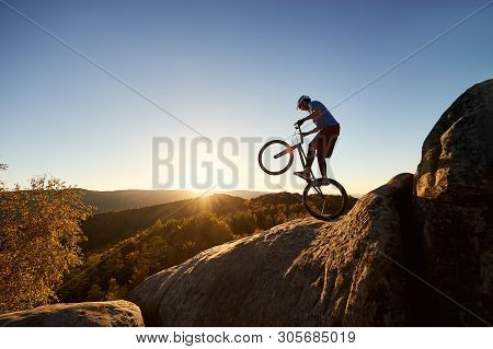 Fearless Cyclist Standing On Back Wheel On Trial Bicycle. Professional Sportsman Rider Balancing On